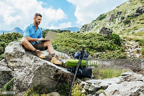 Hiker with laptop sitting on a rock