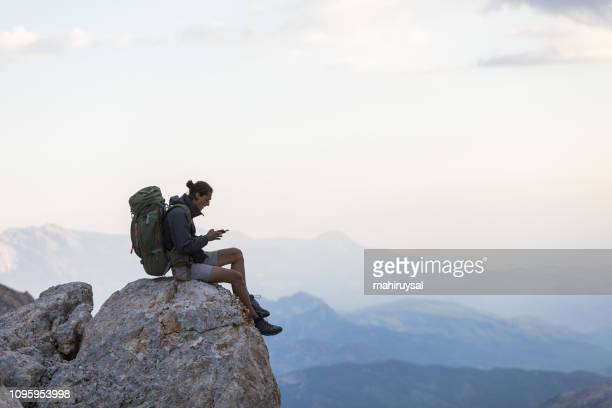 hiker with mobile phone and backpack - cliff stock pictures, royalty-free photos & images