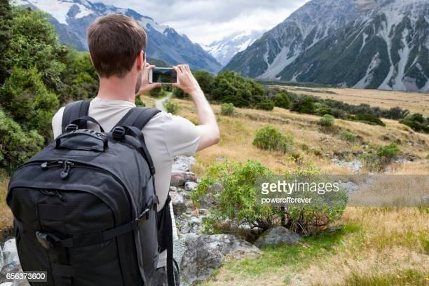 Wanderer mit Smartphone fotografieren Mount Cook der Südalpen in Neuseeland