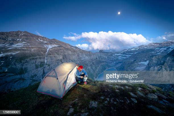 hiker with tent cooking above lake limmernsee, switzerland - tent stock pictures, royalty-free photos & images