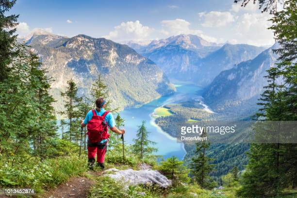 hiker with view to lake königssee and st bartholomä, nationalpark berchtesgaden - königssee bavaria stock photos and pictures