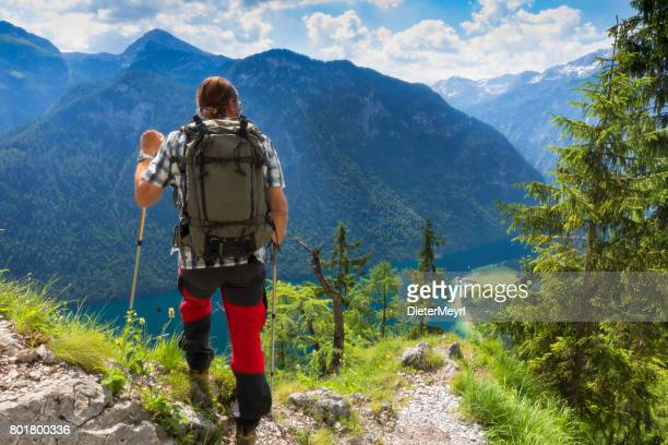 hiker with view to lake königssee and st bartholoma church - berchtesgaden stock photos and pictures