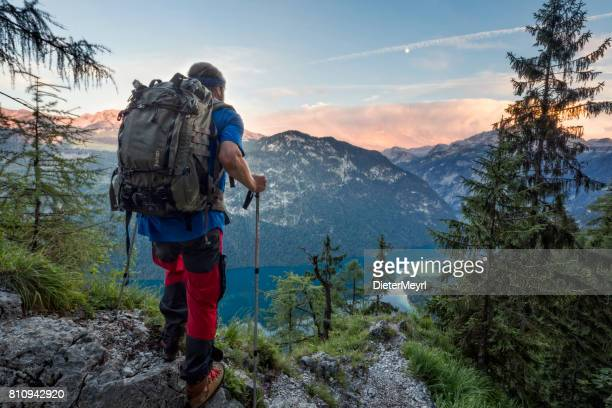 hiker with view to lake königssee and st bartholoma church - königssee bavaria stock photos and pictures