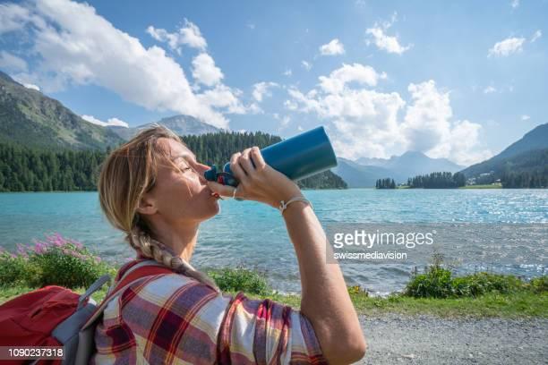 Hiker woman drinking on mountain lake trail from water bottle