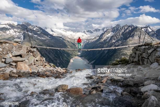 hiker, woman on suspension bridge at the olpererhuette, schlegeis reservoir, schlegeis reservoir, zillertal alps, schlegeiskees glacier, zillertal, tyrol, austria - 北チロル ストックフォトと画像