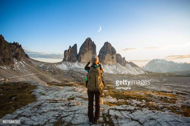 Hiker woman photographs the moon above mountain landscape