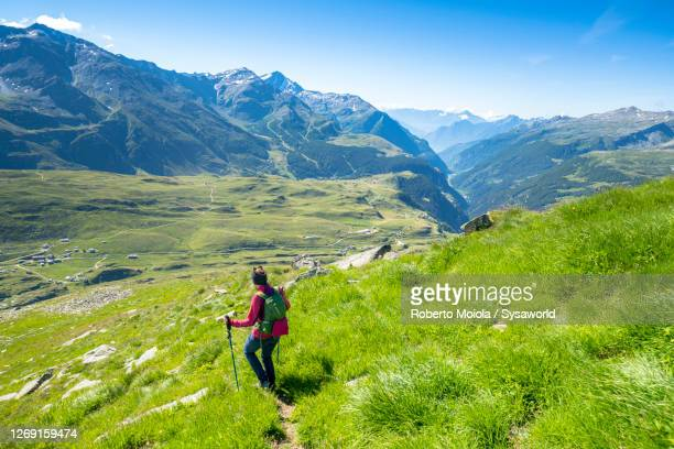 hiker woman walking towards andossi, madesimo, italy - mediterranean culture stock pictures, royalty-free photos & images