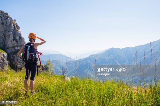 hiker woman walks on mountain meadow - work helmet stock pictures, royalty-free photos & images