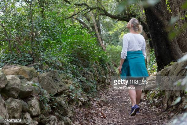 hiker wonders down pathway through forest - pedal pushers stock pictures, royalty-free photos & images