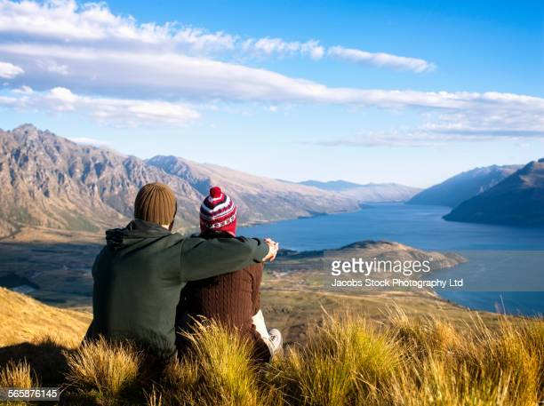 Hikers admiring scenic view from hilltop, Queenstown, South Island, New Zealand