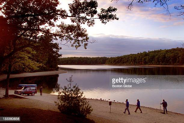 Hikers and fishermen on the beach at sunset at Walden Pond which is just off of Rt 2