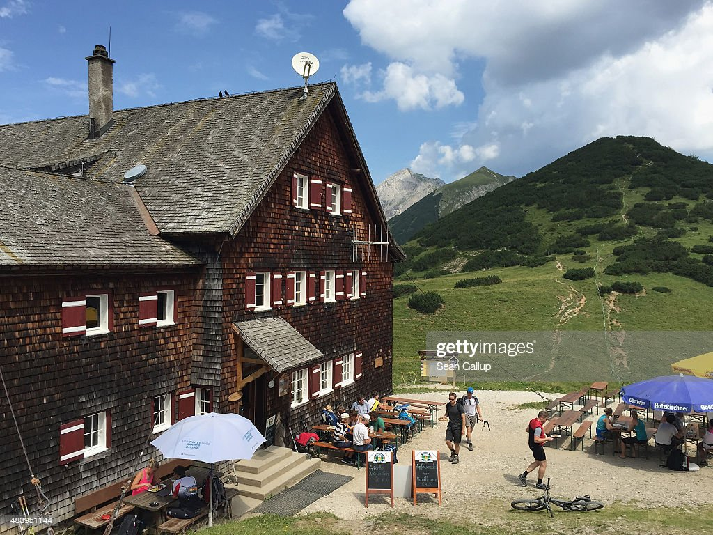Hikers and mountain bikers relax at Falkenhuette hut in the Karwendel mountain range on August 8, 2015 near Herrenhaeuser, Austria. The Karwendel mountain range, part of the Austrian Alps, is located in central Tyrol and is a popular summer destination for mountain bikers, climbers and hikers. Mountain huts operated by alpine clubs and scattered across the region offer food and shelter.