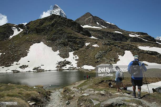 Hikers approach a chapel among snow at Schwarzsee lake under the Matterhorn on July 1 2013 near Zermatt Switzerland Zermatt is among Switzerland's...