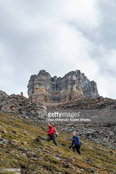 hikers ascend mountain trail, below cliff walls - ascent xmedia stock pictures, royalty-free photos & images