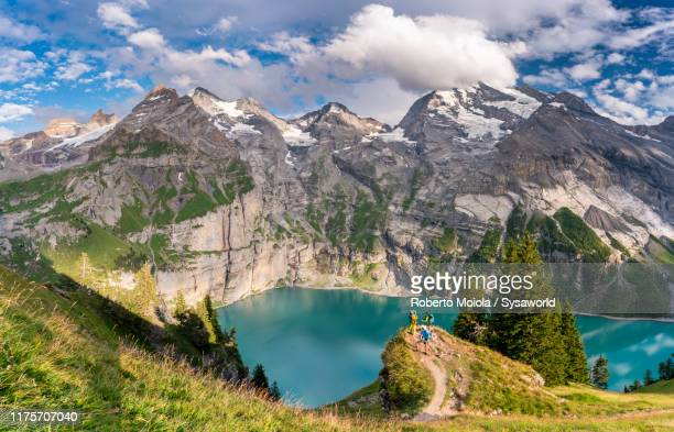 hikers at oeschinensee lake, bernese oberland, switzerland - swiss alps stock pictures, royalty-free photos & images