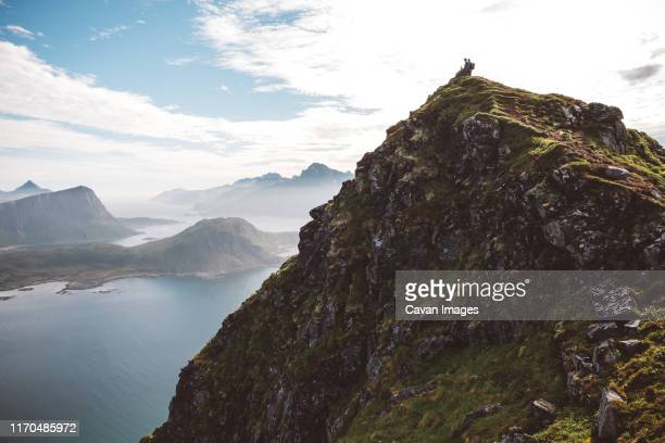 hikers at the top of the mountain with a scenic view of the islands - noord stockfoto's en -beelden