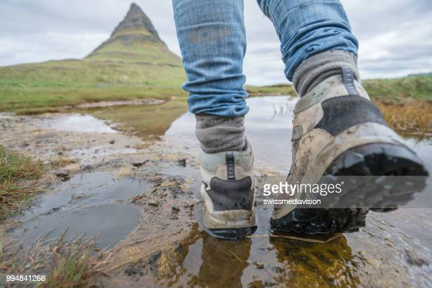 Hiker's boots at Kirkjufell mountain standing near fjord, Iceland