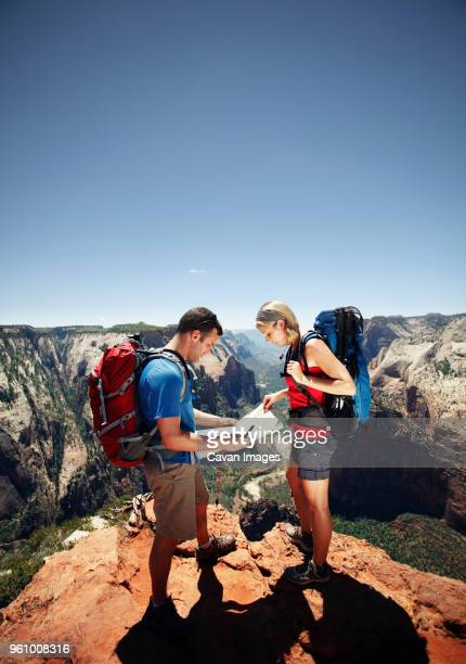 Hikers checking map at mountain cliff against clear sky