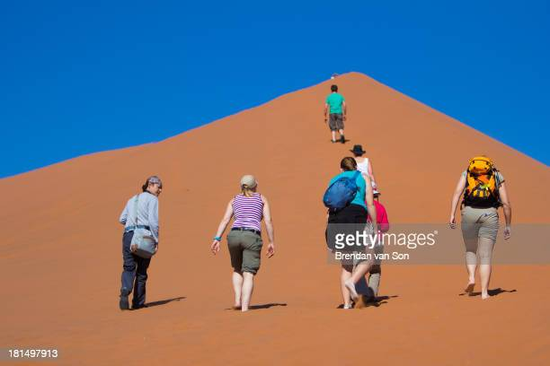 CONTENT] Hikers climbing a dune in Sossusvlei Namibia