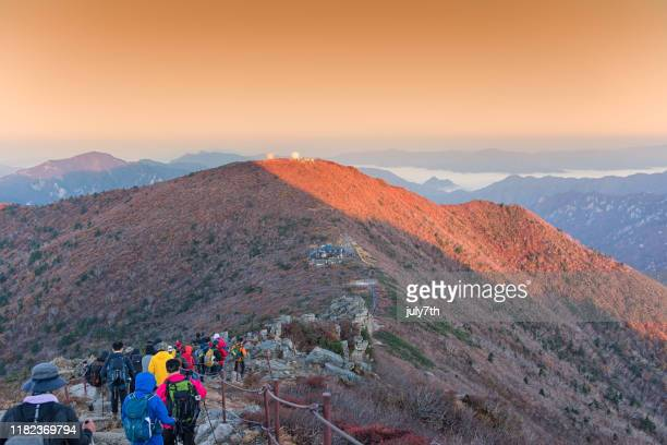 hikers climbing down mountain peak - gangwon province stock pictures, royalty-free photos & images