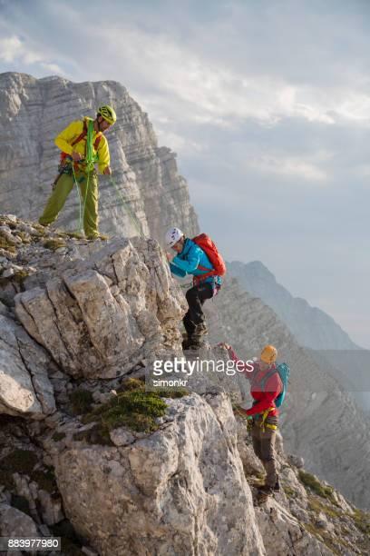 hikers climbing on a rock mountain - alpinismo foto e immagini stock