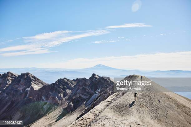 hikers climbing ridgeline at mt st helens with mt adams in background - mount st. helens ストックフォトと画像