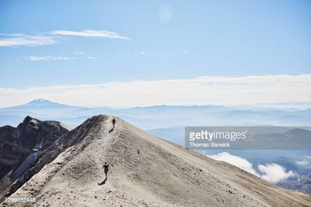 hikers climbing ridgeline at mt st helens with mt adams in background - paisajes de st thomas fotografías e imágenes de stock