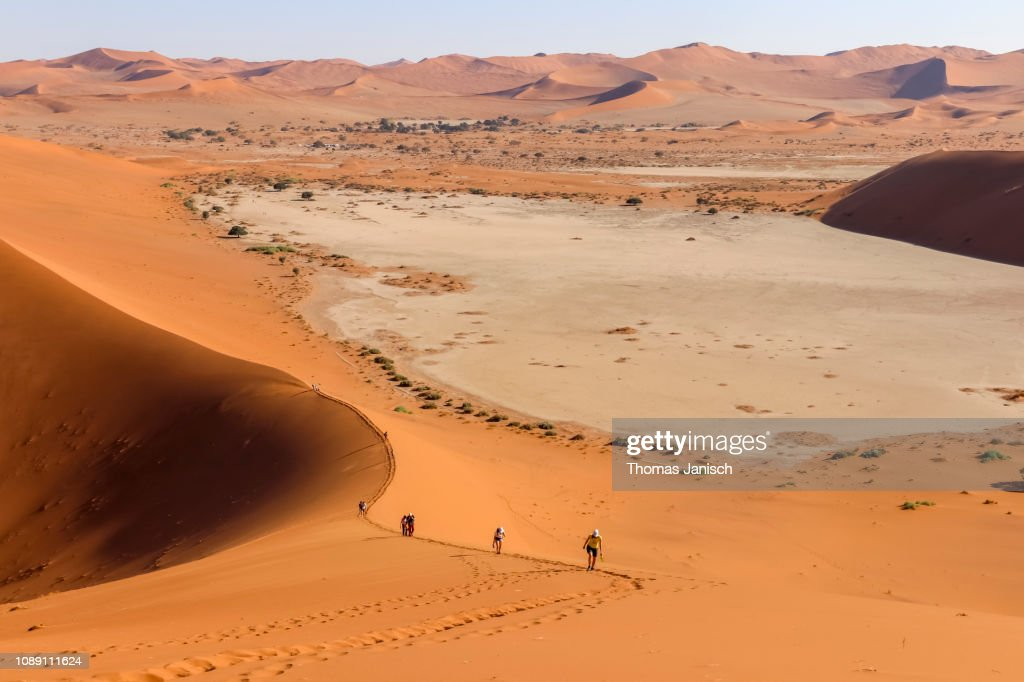 Hikers Climbing The Big Daddy Dune The Tallest Dune Of The