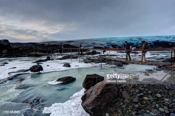hikers crossing glacier melting water on a footbridge - north stock pictures, royalty-free photos & images