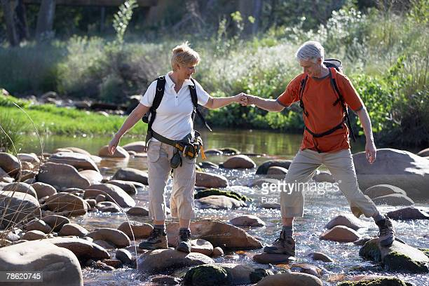 hikers crossing stream - 50 59 years stock pictures, royalty-free photos & images