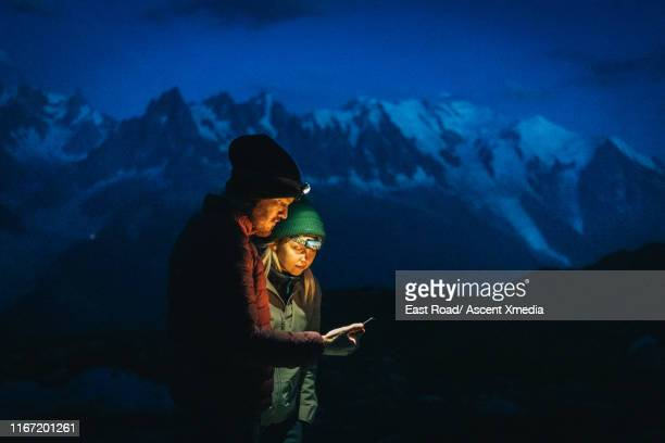 hikers explore mountain landscape, at dusk - direction stock pictures, royalty-free photos & images