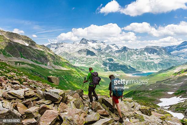 hikers explore the mountain valley - lombardy stock pictures, royalty-free photos & images
