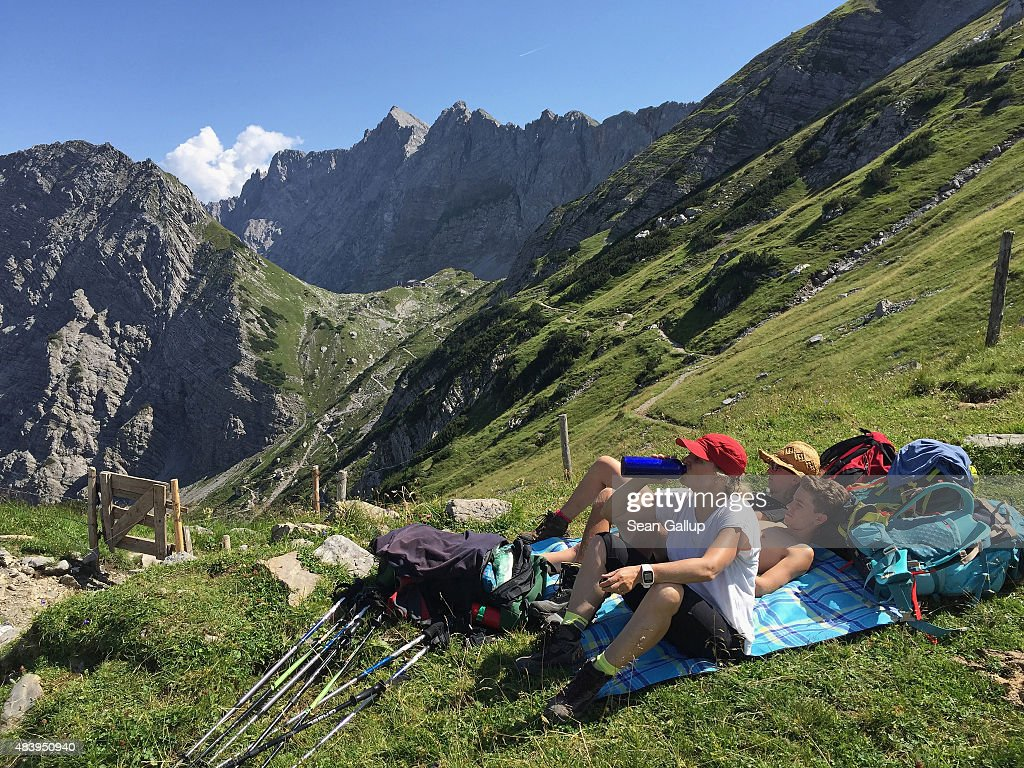 Hikers, family members of the photographer, on day three of a four-day, 50km hike across the Karwendel mountain range take a break as their destination for the day, the Lamsenjochhuette hikers' and climbers' hut, stands behind in the center of the image on August 9, 2015 near Eng Alm, Austria. The Karwendel mountain range, part of the Austrian Alps, is located in central Tyrol and is a popular summer destination for mountain bikers, climbers and hikers. Mountain huts operated by alpine clubs and scattered across the region offer food and shelter.