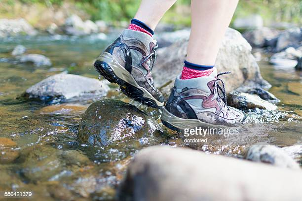 Hikers feet walking on stones in shallow stream