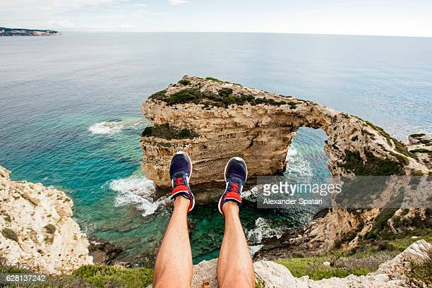 Hiker's feet with the view towards Tripitos Arch, Paxos island, Greece
