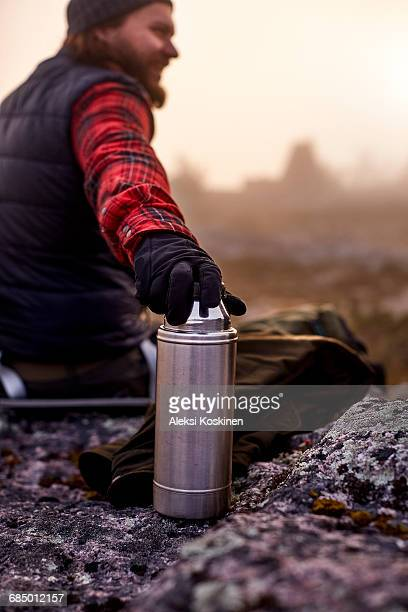Hikers hand resting on coffee flask, Sarkitunturi, Lapland, Finland