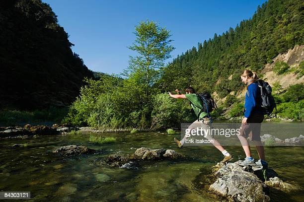 Hikers jumping across river on rocks