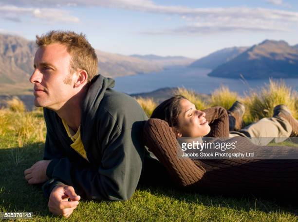Hikers laying on remote hilltop, Queenstown, South Island, New Zealand