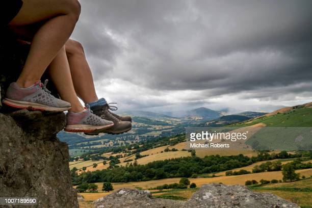 hikers' legs and the view from table mountain (crug hywel) towards sugar loaf in the black mountains, brecon beacons national park, wales - crickhowell foto e immagini stock