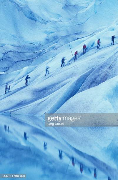 Hikers linked by rope, climbing glacier