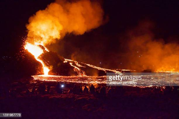Hikers look at the lava flowing from the erupting Fagradalsfjall volcano some 40 km west of the Icelandic capital Reykjavik, on March 26, 2021. - A...