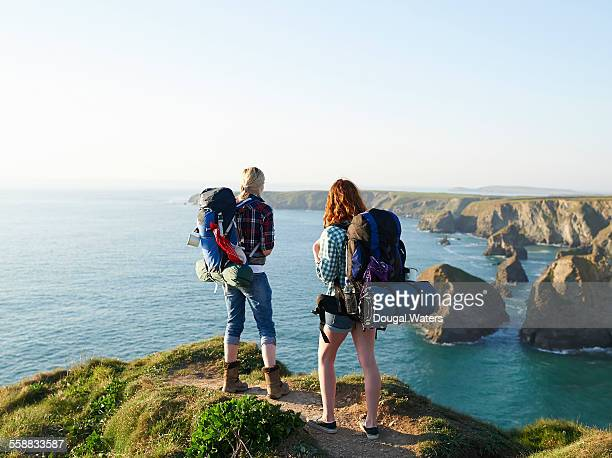 Hikers looking along Atlantic coast from cliff top