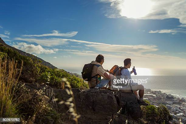 Hikers looking at sea while sitting on rocks