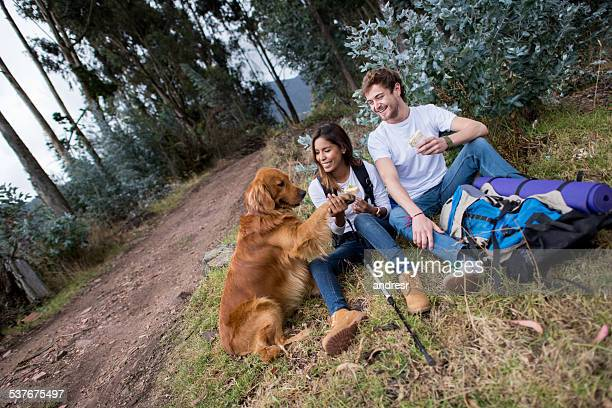 Hikers mountain climbing with a dog