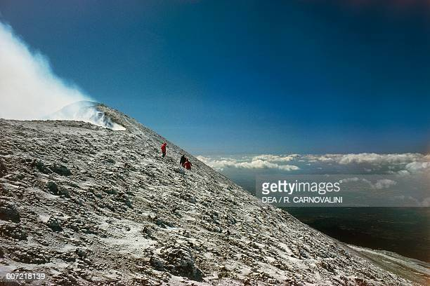 Hikers near Mount Etna central crater with snow Mount Etna nature park Sicily Italy