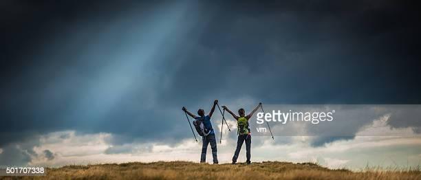 Wanderer auf einer Hochebene im Blick auf schwarze Wolken