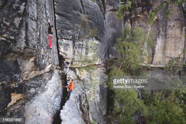 hikers on rocky cliff - andrea rizzi stockfoto's en -beelden