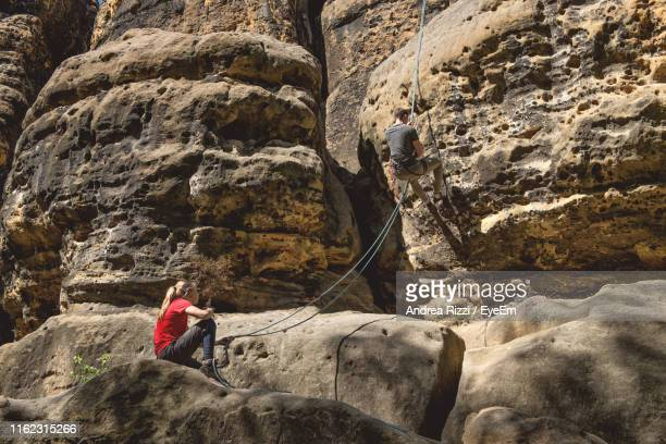 hikers on rocky cliff - andrea rizzi stock pictures, royalty-free photos & images
