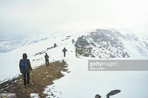 Hikers on snow-covered mountain, Coniston, Cumbria, United Kingdom