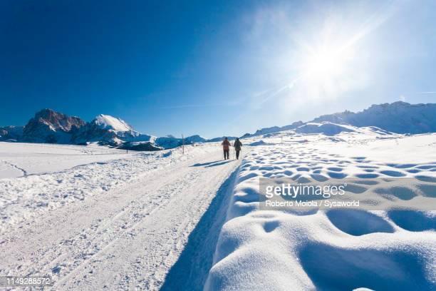 hikers on snowy footpath, seiser alm, italy - alto adige foto e immagini stock